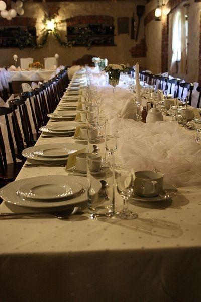 stoły z talerzami, sztućce, szklanki